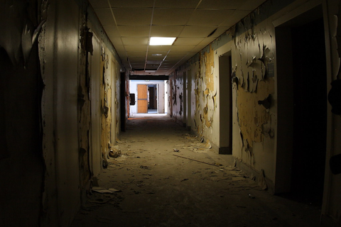 Spooky abandoned hallway. One light still works ...