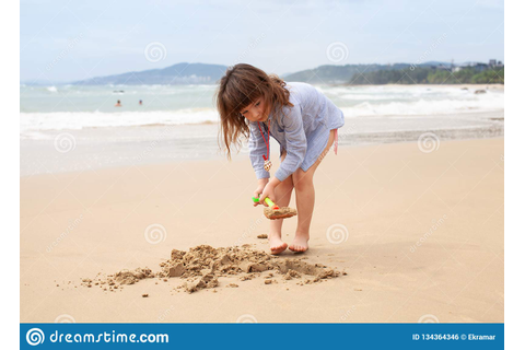 Five-year-old Girl Playing On The Sandy Beach Of The Sea ...